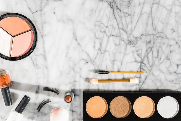 Polvere compatta; smalto; rossetto; ciglia; mascara su sfondo con texture di marmo
