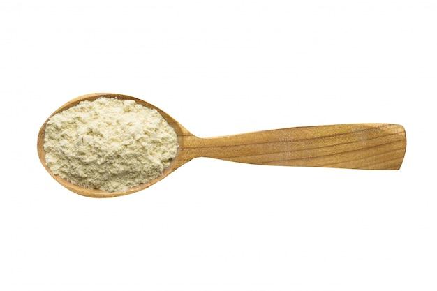 Polvere del fieno greco in cucchiaio di legno isolato su fondo bianco. spezia per cucinare cibo, vista dall'alto.