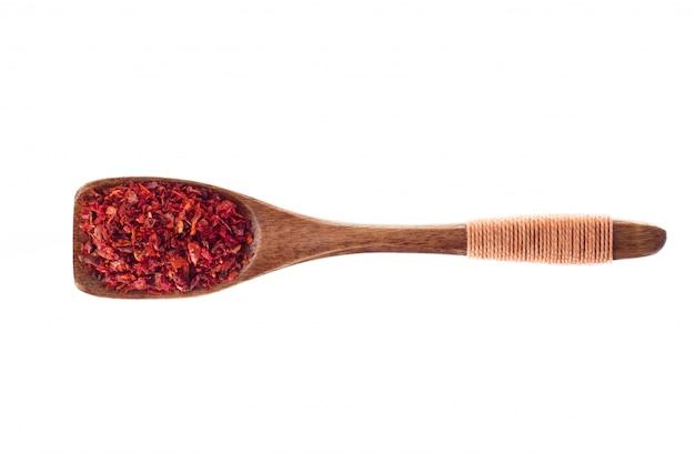 Polvere del pomodoro secca spezia in cucchiaio di legno isolato su un fondo bianco, vista superiore