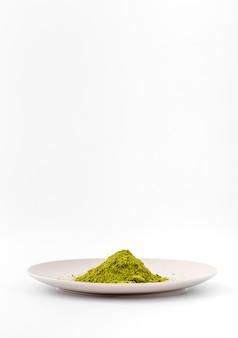 Polvere del tè di matcha di vista frontale su un piatto