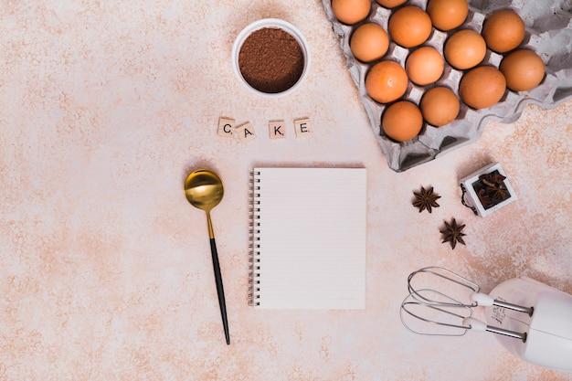 Polvere di cacao; anice stellato; mestolo; blocco note a spirale; e frusta elettrica con blocchi di torta su sfondo con texture