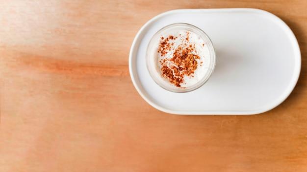 Polvere di cacao sul vetro del caffè sul vassoio sullo sfondo marrone strutturato