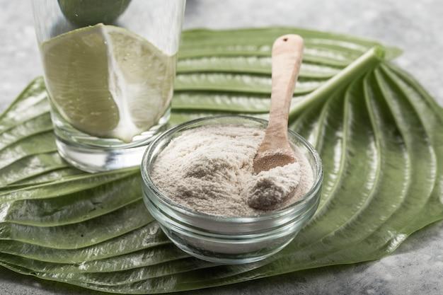 Polvere di collagene e bicchiere d'acqua con fetta di lime; vitamina c . gli integratori di collagene possono migliorare la salute della pelle riducendo rughe e secchezza.