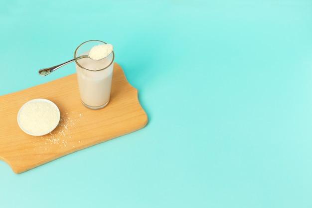 Polvere di collagene e yogurt in un bicchiere con un cucchiaio in cima su sfondo blu.
