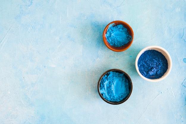 Polvere di colore blu holi nei diversi tipi di ciotole su sfondo dipinto di cemento