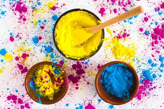 Polvere di colore giallo e blu di holi su fondo bianco