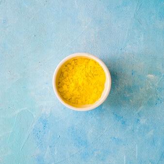 Polvere di colore giallo in una ciotola bianca su sfondo blu di cemento