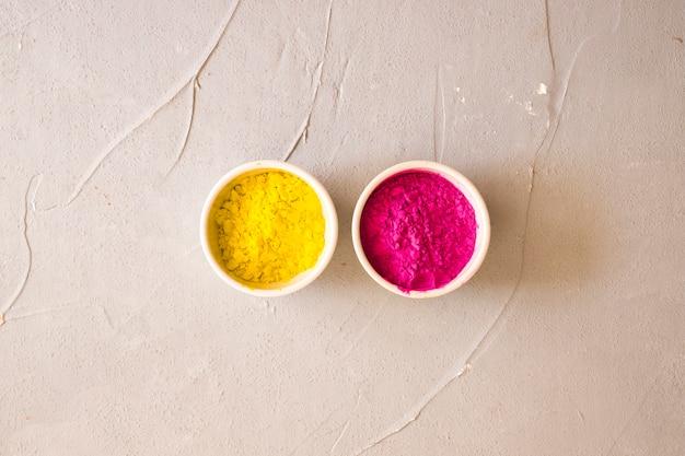 Polvere di colore rosa e giallo nelle ciotole bianche sullo sfondo