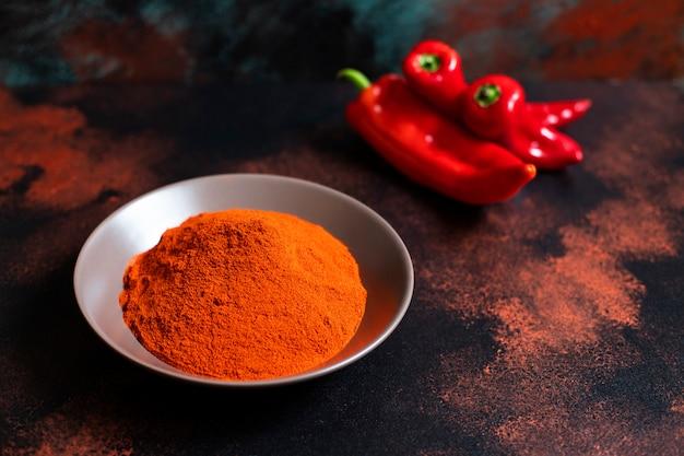 Polvere di paprika in un piatto su uno sfondo colorato orientale. colori brillanti. messa a fuoco selettiva. spazio per il testo. avvicinamento