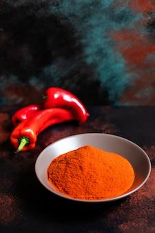 Polvere di paprika in un piatto su uno sfondo colorato orientale. colori brillanti. messa a fuoco selettiva. verticale. spazio per il testo. avvicinamento