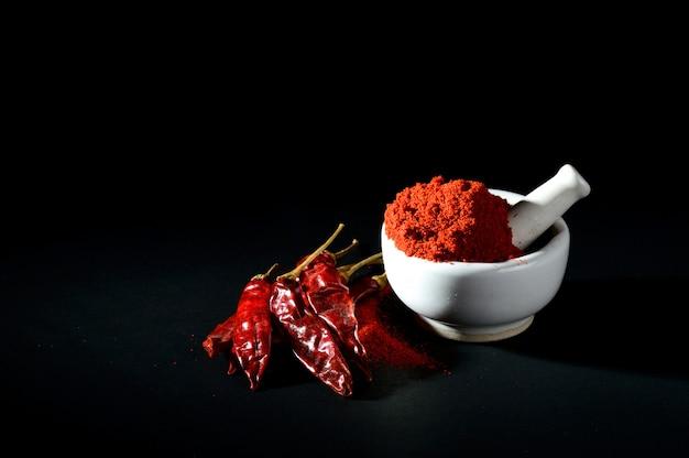 Polvere di peperoncino rosso in pestello con mortaio e peperoncino rosso