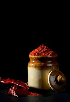 Polvere di peperoncino rosso in una pentola di terracotta