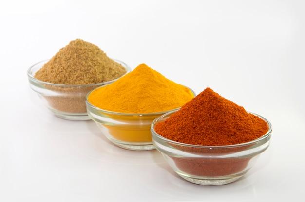 Polvere di spezie: peperoncino, curcuma e coriandolo in ciotola isolata.