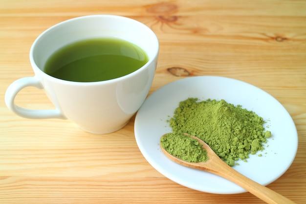 Polvere di tè matcha con un cucchiaio di legno e una tazza di tè verde matcha caldo sul tavolo di legno