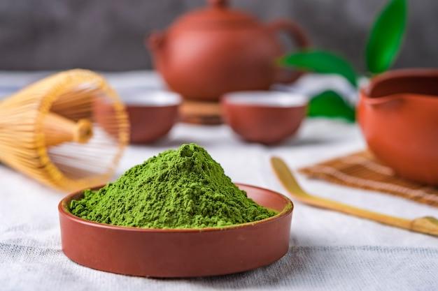 Polvere di tè verde con foglia in un piatto di ceramica sul tavolo, frusta giapponese fatta di bambù per la cerimonia del tè matcha
