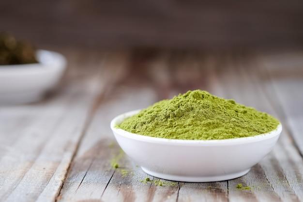 Polvere di tè verde con tè essiccato in tazza bianca