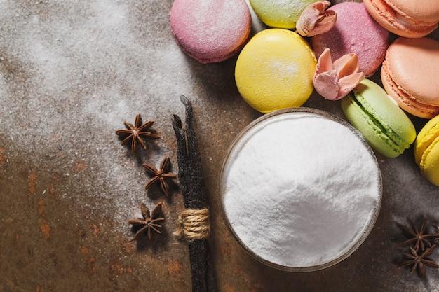 Polvere di vaniglia, baccelli di vaniglia e amaretti colorati. vista dall'alto.