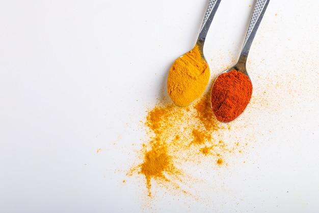 Polvere indiana dei peperoncini rossi e della curcuma in cucchiaio su fondo bianco