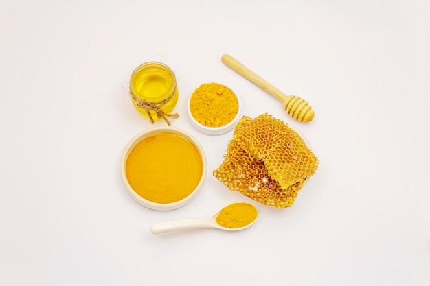 Polvere, miele e favi asciutti della curcuma isolati su fondo bianco