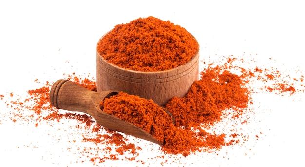 Polvere rossa della paprica in ciotola di legno e mestolo isolati su bianco