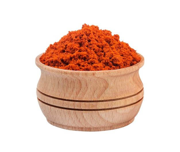 Polvere rossa della paprica in ciotola di legno isolata su fondo bianco