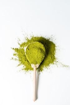 Polvere verde di matcha in cucchiaio di legno isolato
