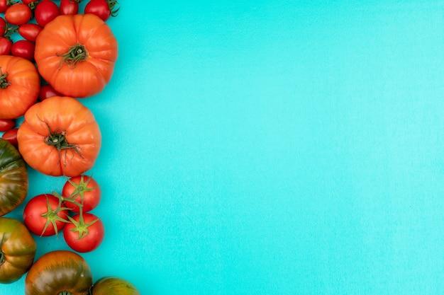 Pomodori a sinistra del telaio con copia spazio sulla superficie blu chiaro