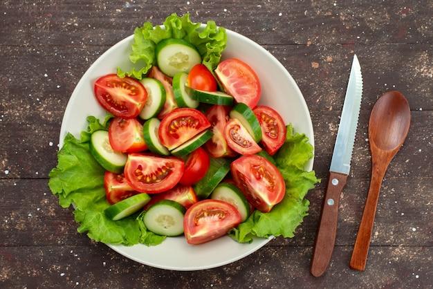Pomodori affettati vista superiore con i cetrioli dentro il piatto bianco con insalata verde su marrone, sald fresco di verdure del pranzo dell'alimento