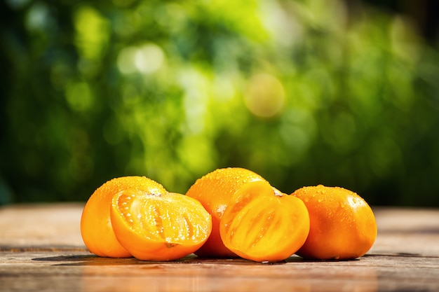 Pomodori arancioni sul tavolo su uno sfondo verde