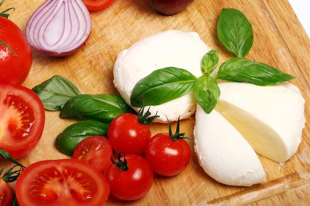 Pomodori, basilico e mozzarella su tavola di legno