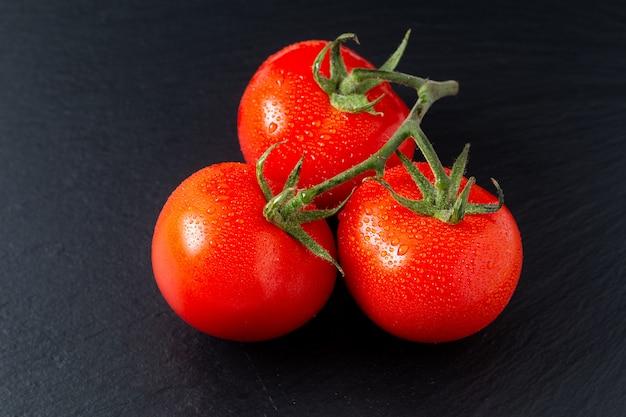 Pomodori biologici sul bordo di ardesia nera con spazio di copia