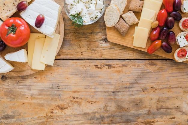 Pomodori; blocchi di formaggio e uva sulla scrivania in legno