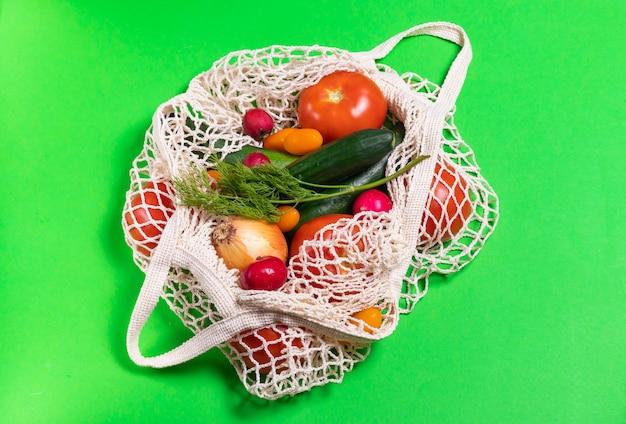 Pomodori, cetrioli, cipolle, ravanelli e aneto in un sacchetto di stringa su sfondo verde