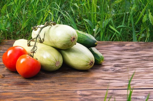 Pomodori, cetrioli e zucca su tavole di legno con erba verde sullo sfondo.