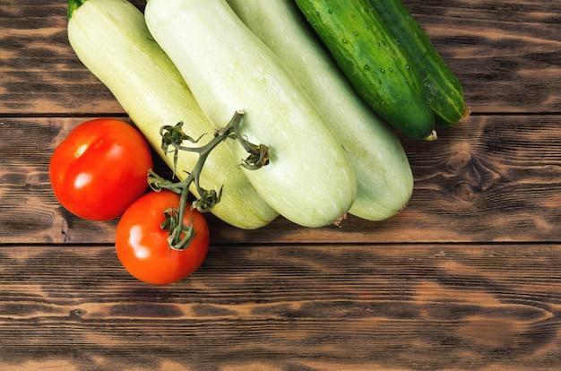Pomodori, cetrioli e zucca su tavole di legno