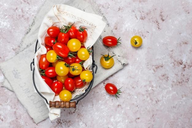 Pomodori ciliegia di vari colori, pomodori ciliegia gialli e rossi in un canestro su fondo leggero