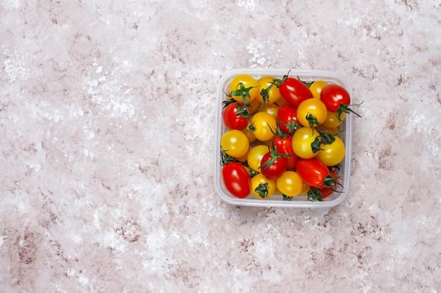 Pomodori ciliegia di vari colori, pomodori ciliegia gialli e rossi su sfondo chiaro