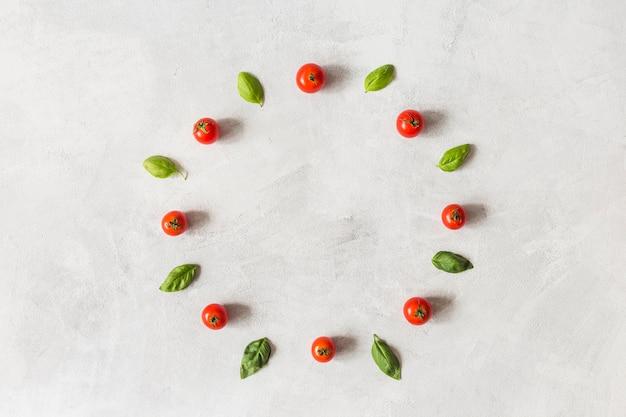 Pomodori ciliegia e foglie di basilico disposte in cornice circolare su sfondo bianco strutturato