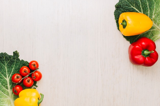 Pomodori ciliegia e peperoni su foglia di cavolo verde sopra l'angolo della superficie in legno con lo spazio della copia per il testo