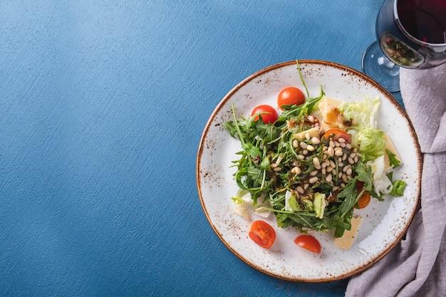 Pomodori ciliegia e pinoli dell'insalata della rucola in piatto. vista dall'alto.