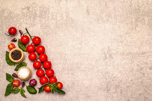 Pomodori ciliegia e spezie maturi su un fondo di pietra