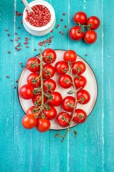 Pomodori ciliegia e spezie su una tavola di legno del turchese