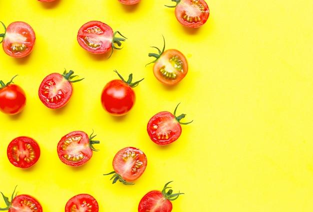 Pomodori ciliegia freschi, taglio intero e mezzo isolato su giallo