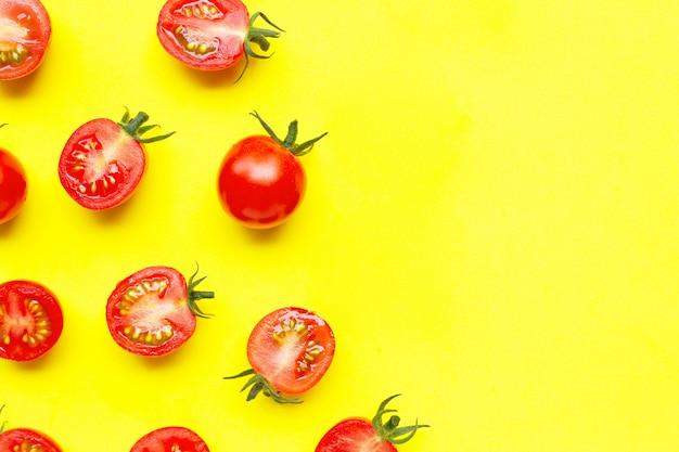 Pomodori ciliegia freschi, taglio intero e mezzo isolato su giallo.