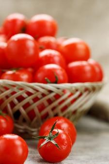 Pomodori ciliegia maturi e succosi con gocce di umidità in un cestino di vimini. vecchio tavolo di legno, attorno alla tela di tela