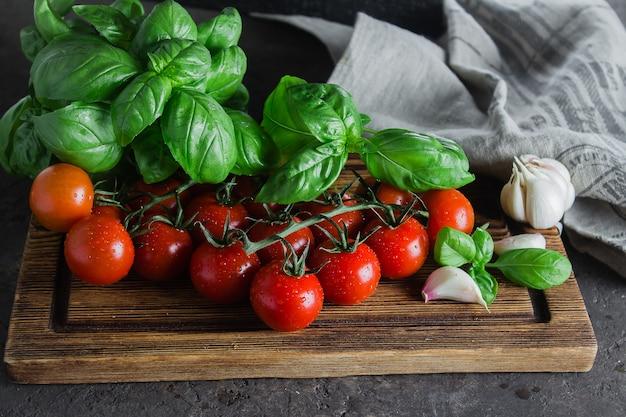 Pomodori ciliegia organici con basilico e aglio sul tagliere