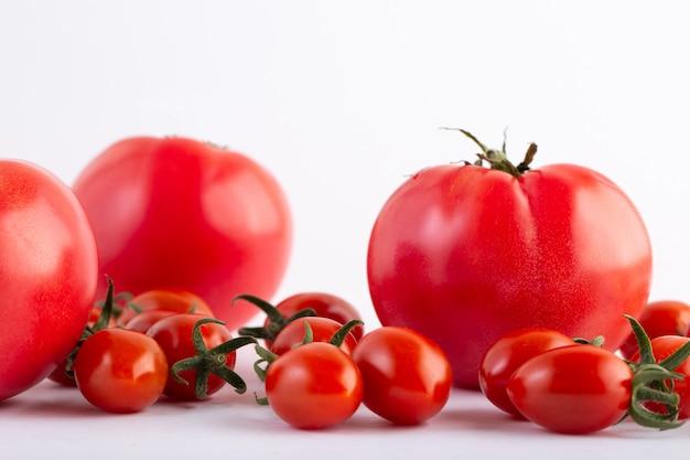 Pomodori ciliegia pomodori rossi rossi su fondo bianco