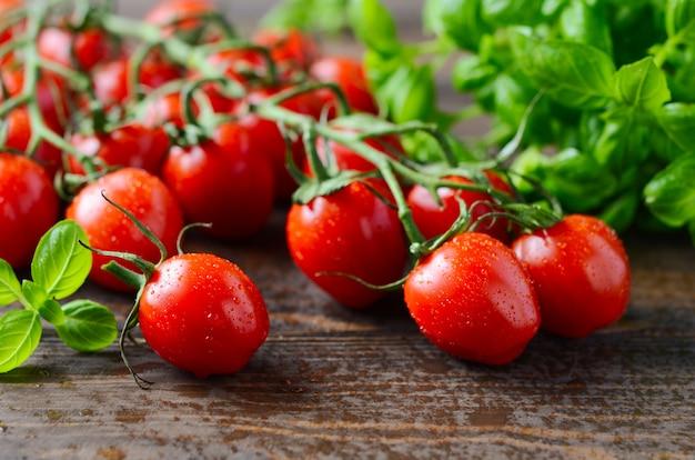 Pomodori ciliegia rossi freschi con basilico su una tavola di legno rustica.