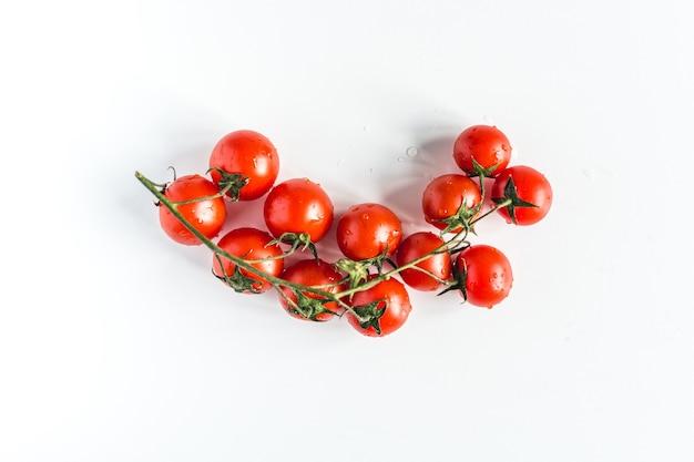 Pomodori ciliegia rossi freschi maturi su sfondo bianco