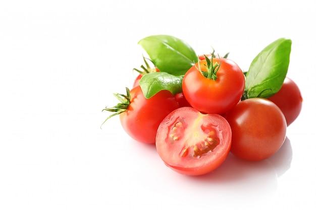Pomodori ciliegia rossi maturi e basilico isolati su fondo bianco
